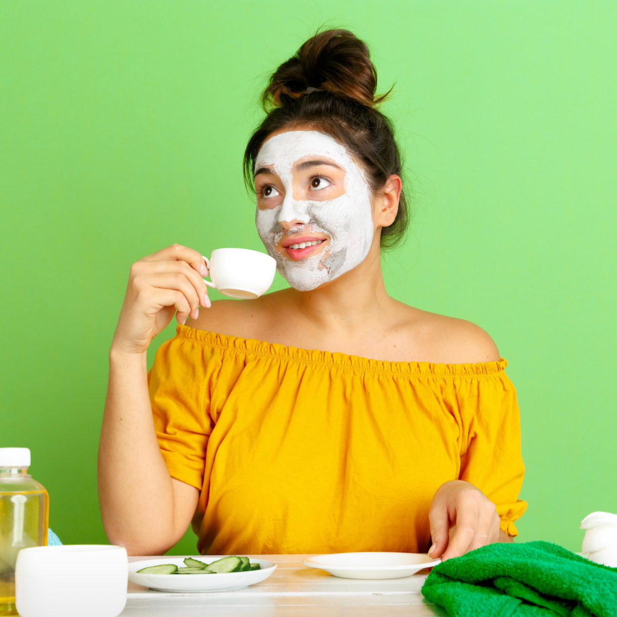 Young woman drinking tea and wearing a skincare mask for her evening routine.
