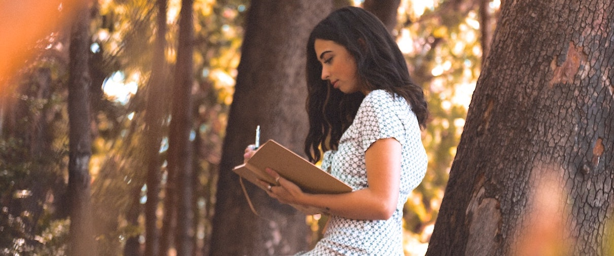 girl using a bullet journal for mental health in the forest.