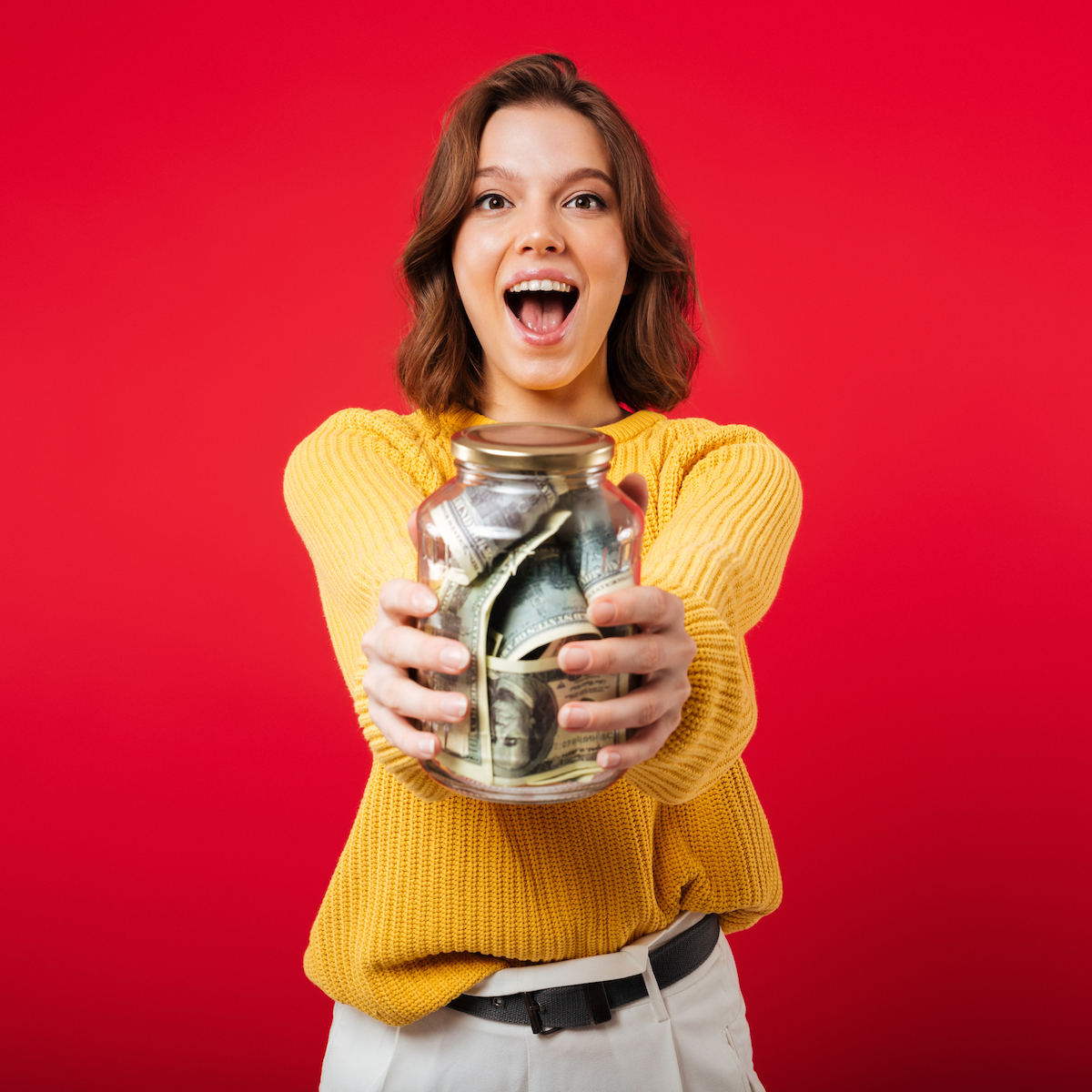 Portrait of an excited woman showing jar full of money banknotes isolated over pink background