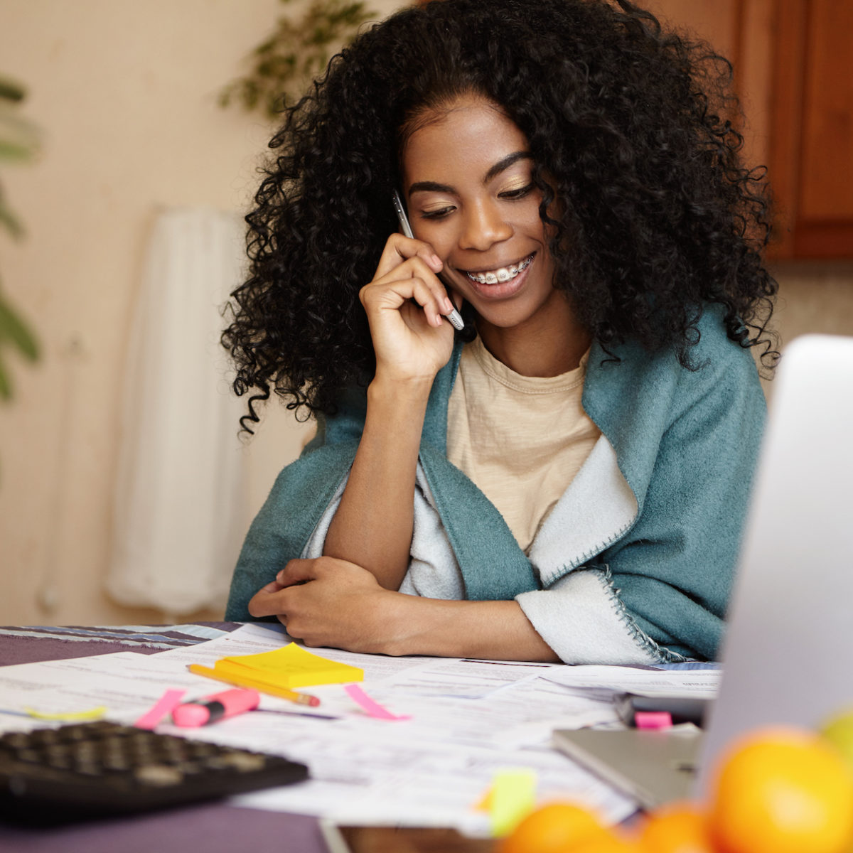 Portrait of young woman with braces smiling happily, talking on phone while sitting at kitchen table with calculator and laptop pc, managing family budget