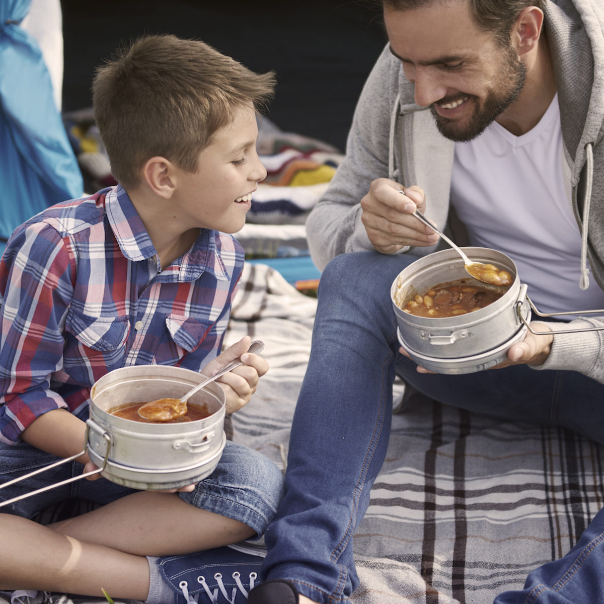 Father and son sharing a camping meal out of mess kit tins on a picnic blanket in front of a tent.