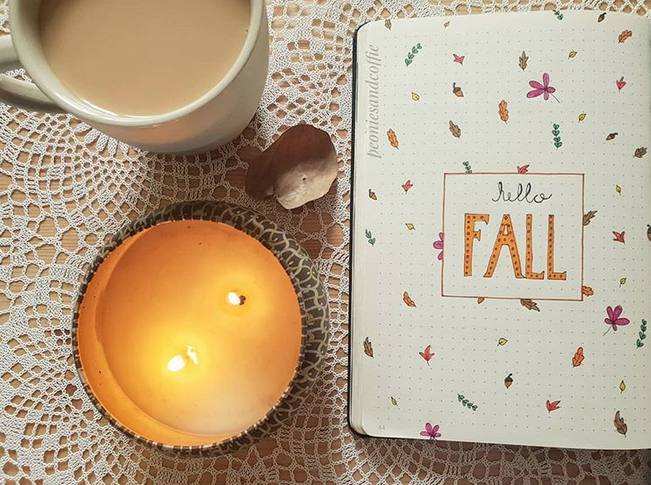 A fall bullet journal cover page with illustrations of dainty autumn leaves, and a table with candles and a latte.