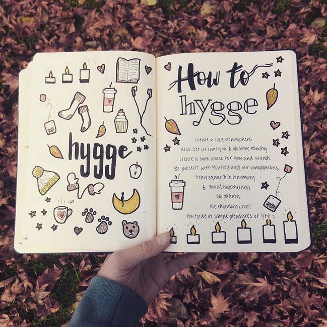 Bullet journal held in front of fallen leaves, with cozy theme doodles of candles, mittens, cupcakes, and tea.