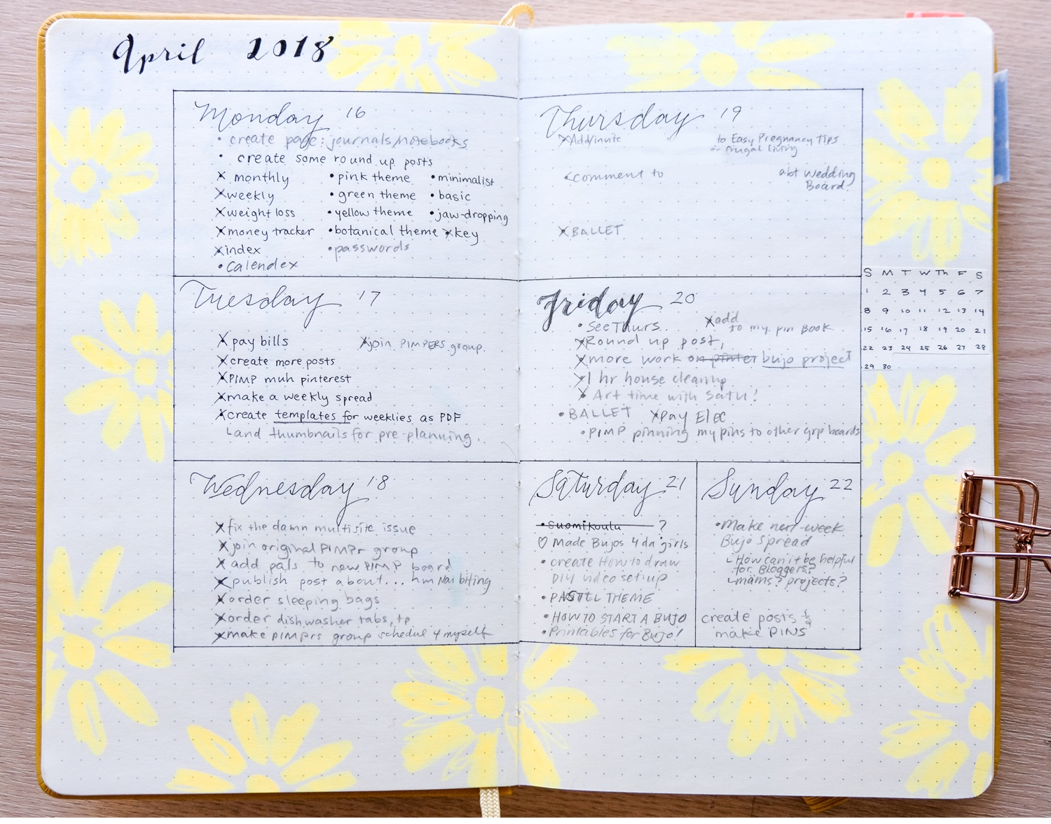 A minimal style bullet journal weekly spread featuring yellow daisy style flowers.