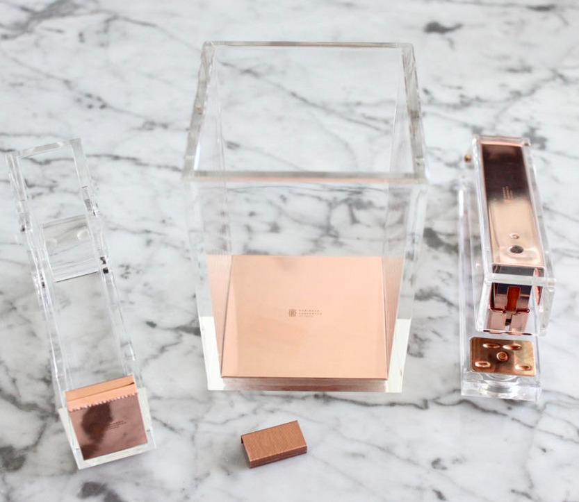 An acrylic desk set with rose gold accents: a stapler, rose gold staples, a pen cup, and tape dispenser.