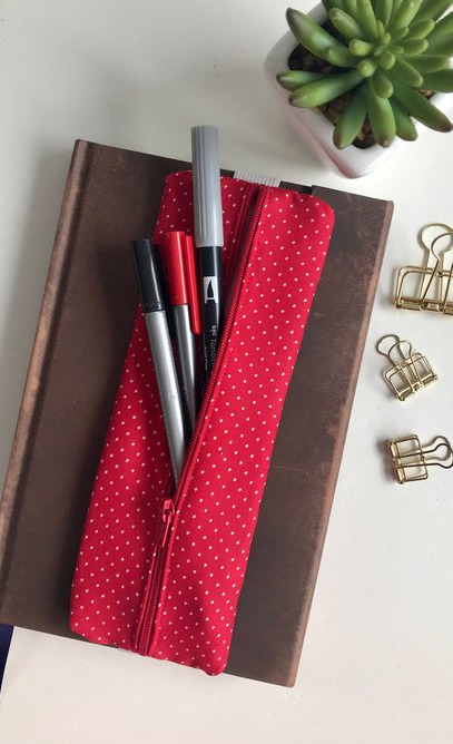 a red zip up bullet journal pen case gift idea that attaches to the cover of the notebook to hold pens.