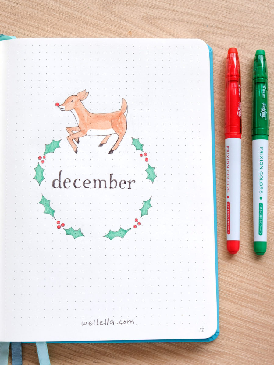 """A bullet journal page with an illustration of holly and a reindeer encircling the word """"december."""""""