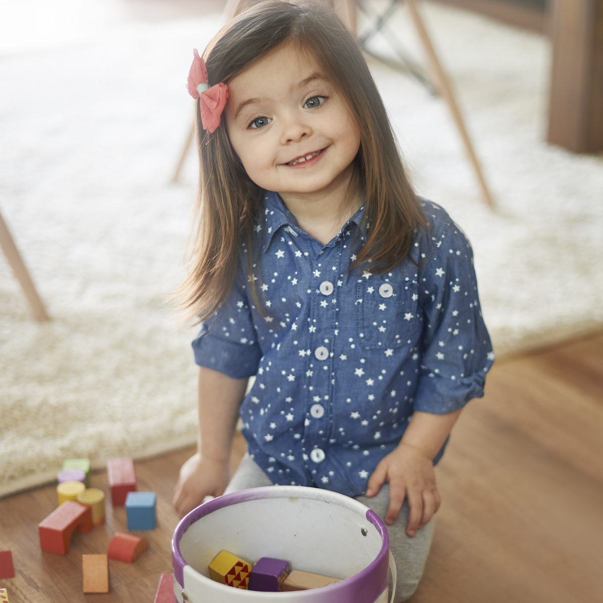 Adorable little girl smiling at the camera as she picks up toy blocks and puts them in a bucket.