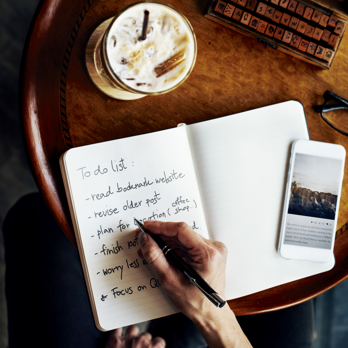 Close up view of a hand writing a to do list in a bullet journal at a cafe table.