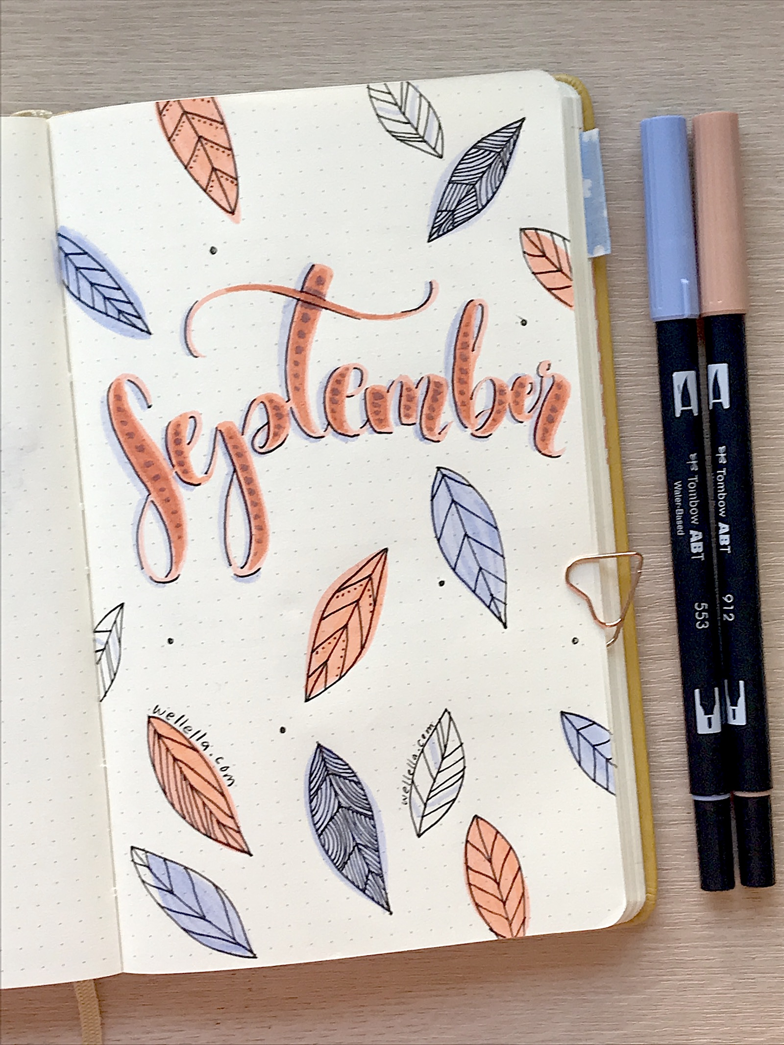 A september bullet journal page with boho style leaves and hand lettering with coral orange and lavender purple markers.