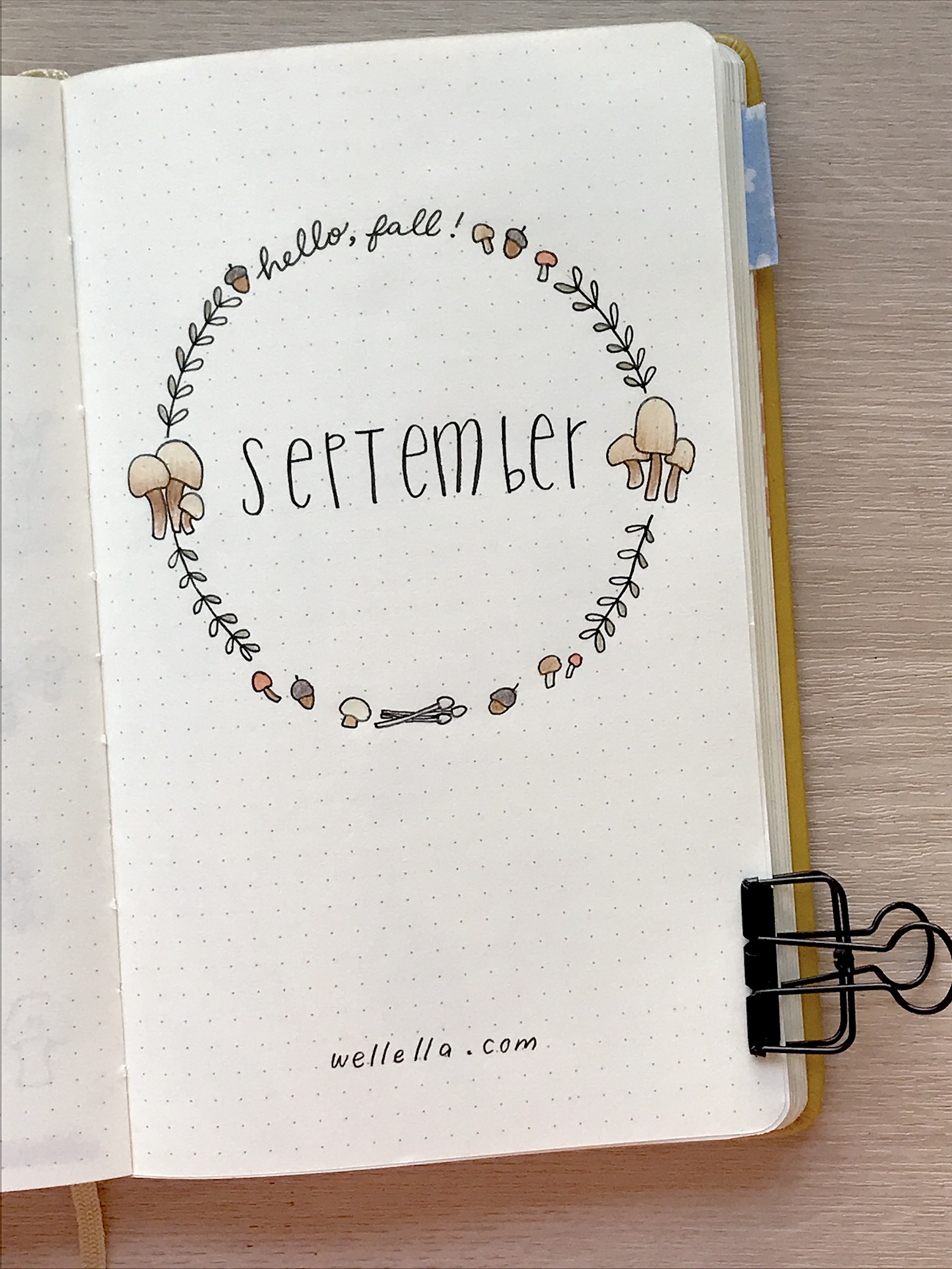 """A september bullet journal cover page with printed text that reads """"September"""" and a wreath of hand-drawn fall leaves, acorns, and mushrooms."""