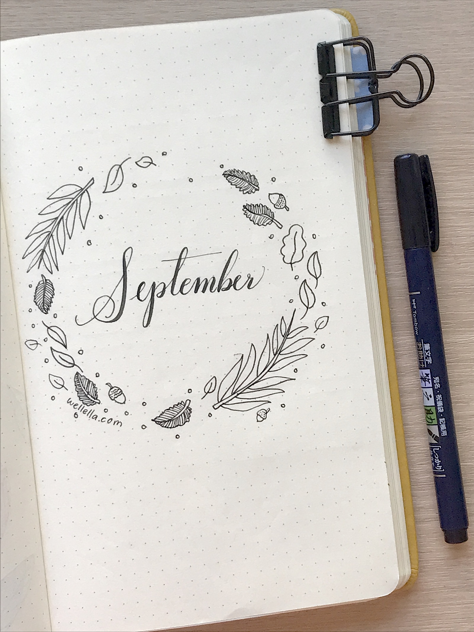 """A september bullet journal cover page with cursive text that reads """"September"""" and a wreath of hand-drawn fall leaves and acorns."""